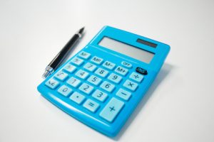 blue calculator and pen