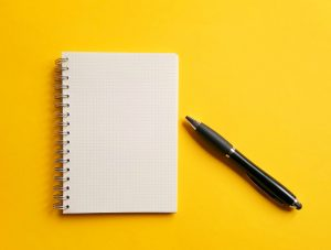 notepad and pen on yellow background