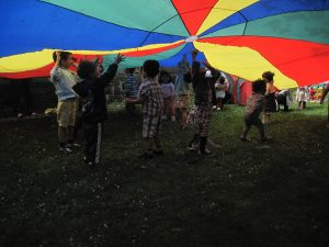 kids having fun playing under a colourful sheet